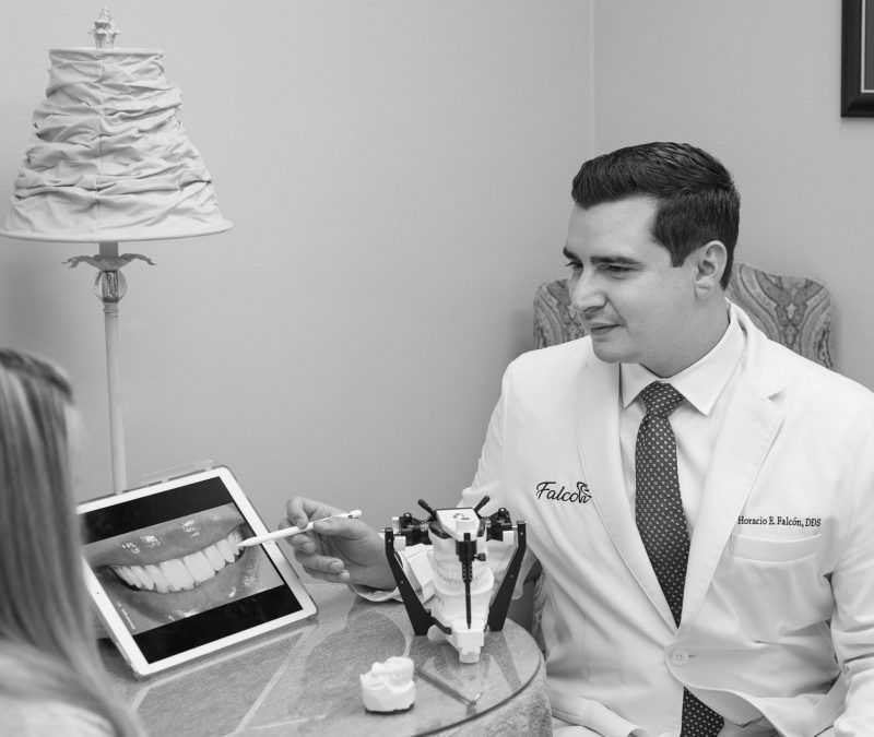 Black and white image of Dr. Falcon reviewing procedure results on an ipad with a client seated